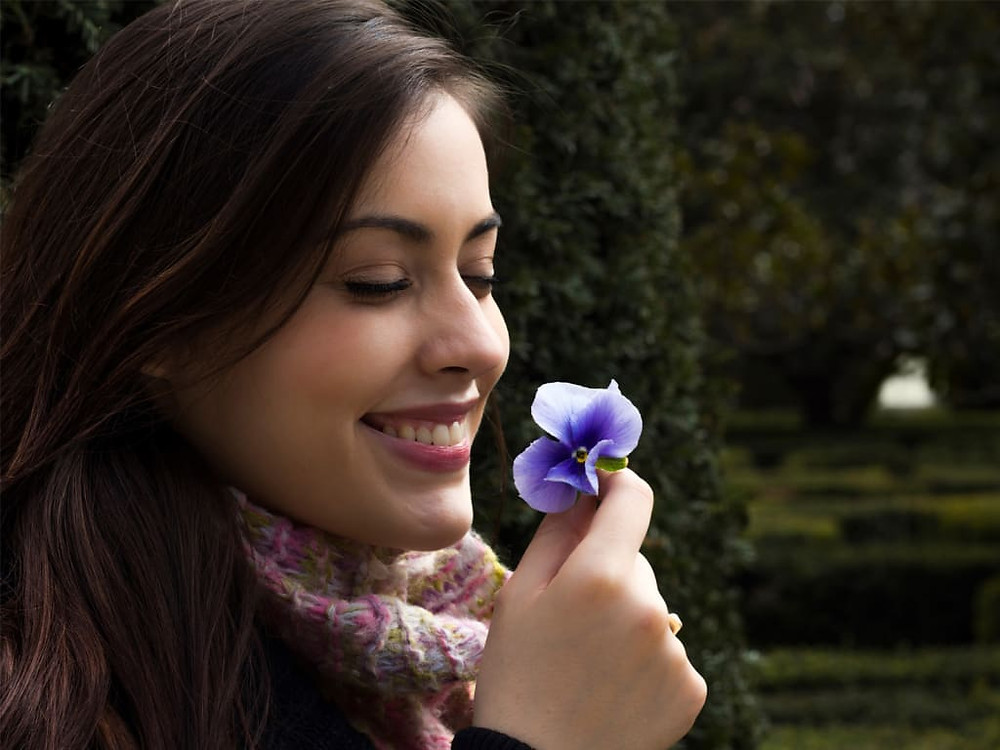 woman smiling while holding purple flower