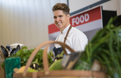 Jamie Humby Melbourne Food Stylist on stage performing a cooking demonstration
