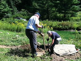 Volunteers setting rocks in wildflower garden