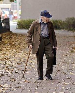 photo-of-elderly-man-walking-on-pavement