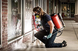 Pest control technician treating for bugs outside a commercial complex