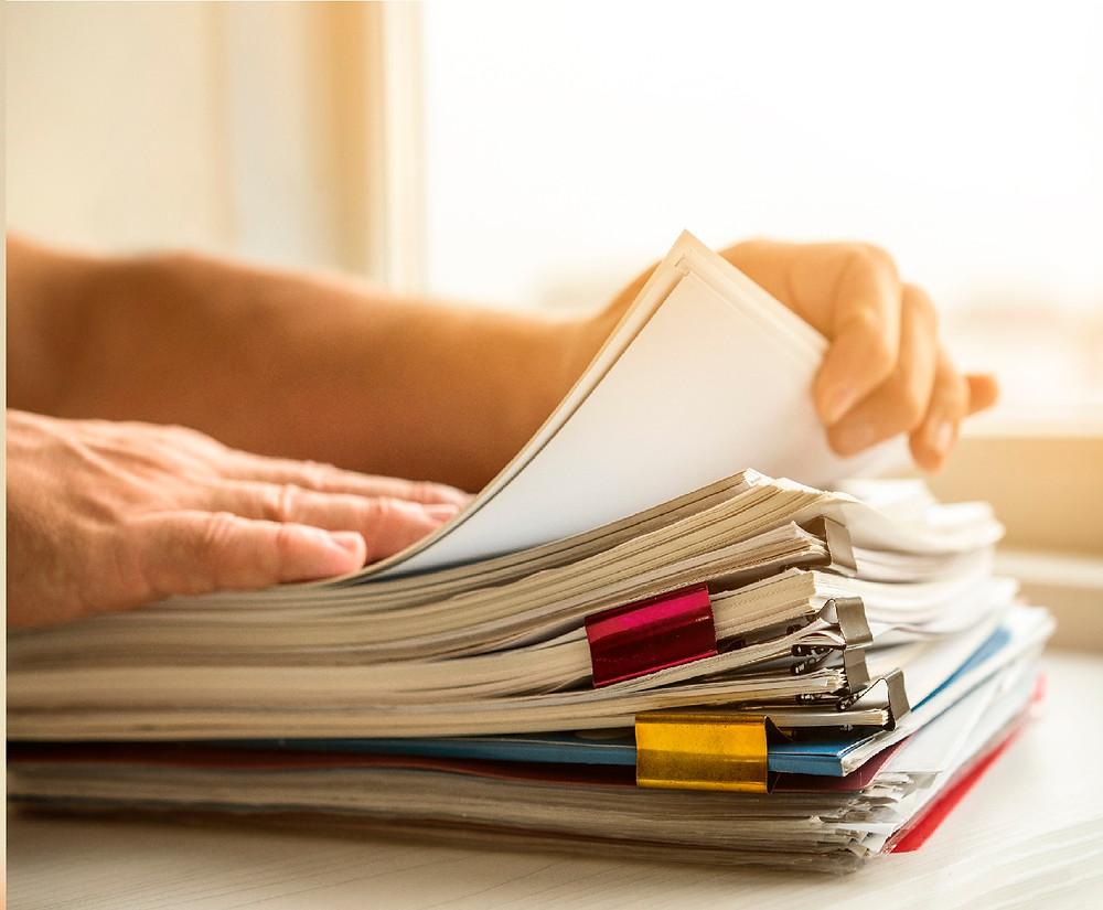 mãos procurando por algo em uma pilha de documentos