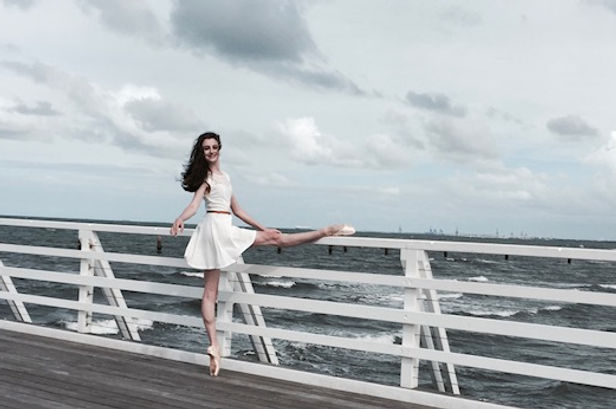 Beautiful and feminine Trienawear ballerina Breana Drummond in a ballet pose at the beach in New Zealand
