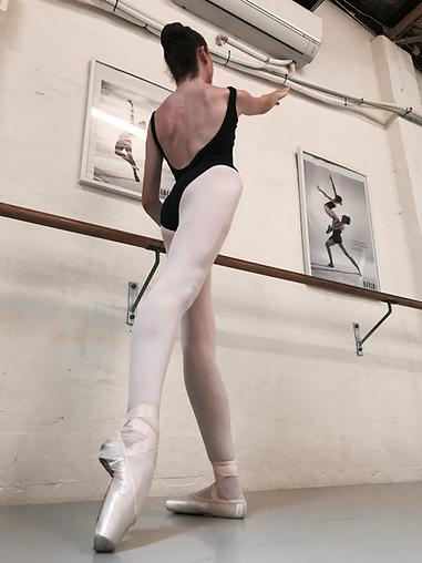 Beautiful and feminine Trienawear ballerina Breana Drummond practicing an arabasque tendu at the ballet barre