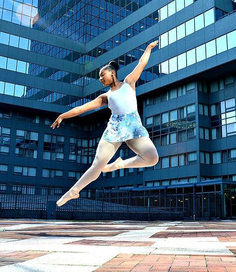 Beautiful, elegant, feminine ballerina ambassador Sage Sarai wearing Trienawear leotard and floral print skirt