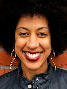 Erin Jones Brick 13 Partner Black woman light brown skin afro red lipstick big smile dimples