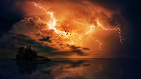 Dark horizon sky over water with lightning, flock of birds, and clouds