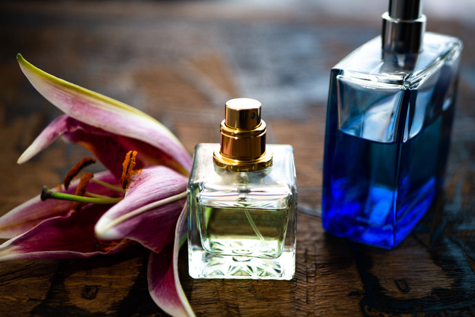 Perfume bottles surrounded by lily petal