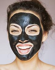 Femme avec un masque visage noir au charbon actif en poudre