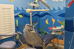 Photo of the dental chairs and the beautiful mural on the wall of the ocean.