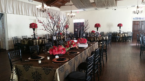 Photo of north hall decorated with red flowers, gold table cloths, place settings and black chairs.