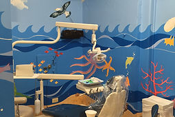 A photograph of the dental hygienist chair in the Children's Dental Clinic with ocean mural.