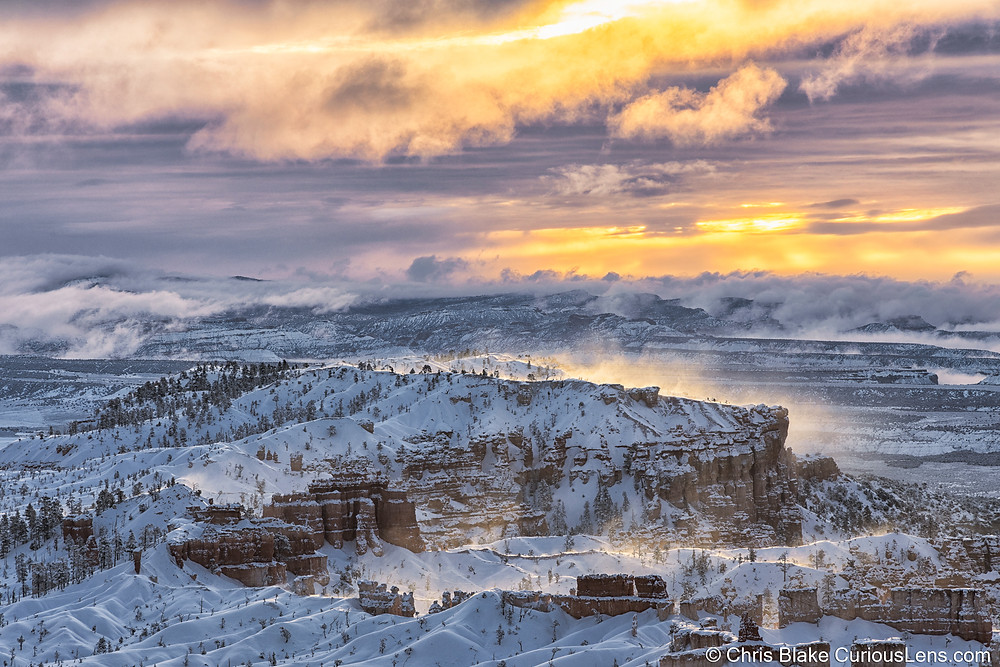 A magnificent winter sunrise over Bryce Canyon National Park. Yellows, pinks, and purples illuminate the sky over the snow-covered trees, striated rocks and hoodoos of the Park