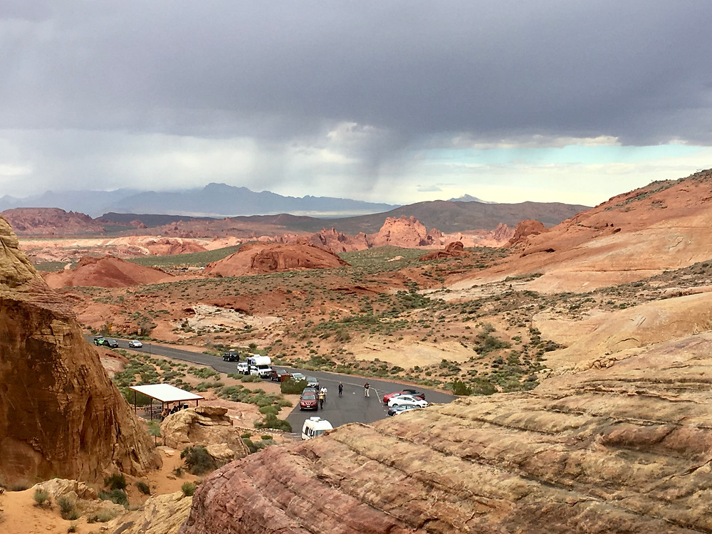 Grey stormclouds loom over brilliant red rocks in the Valley of Fire in Eastern Nevada. A somewhat crowded road winds throughout