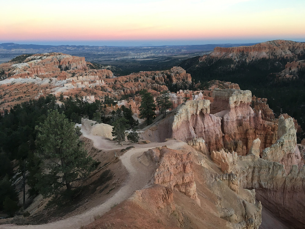 Sun setting over the hoodoos and striated rock structures of Bryce Canyon National Park in Utah
