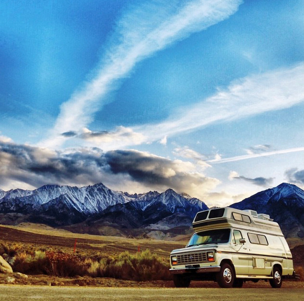 The Spirit Of The West van parked on US Route 395 in front of the staggeringly beautiful Sierra Nevada Range, with streaking clouds amidst blue skies overhead