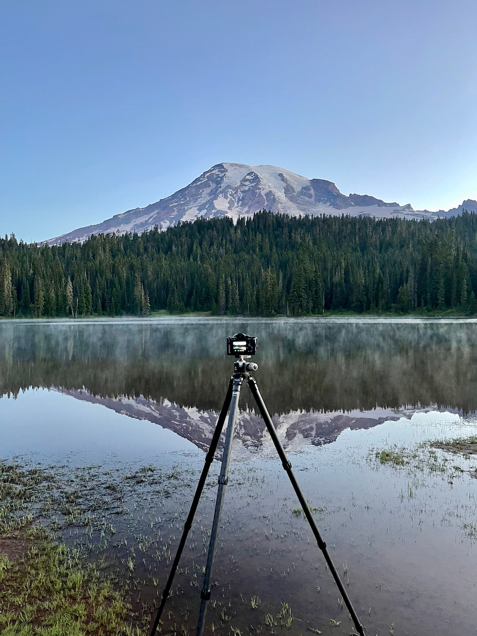 A camera mounted on a tripod at the shore of a crystal clear reflective lake, photographing the glory of the enormous mountain rising above the trees on the opposite shore - and the reflection of all of this in the water below