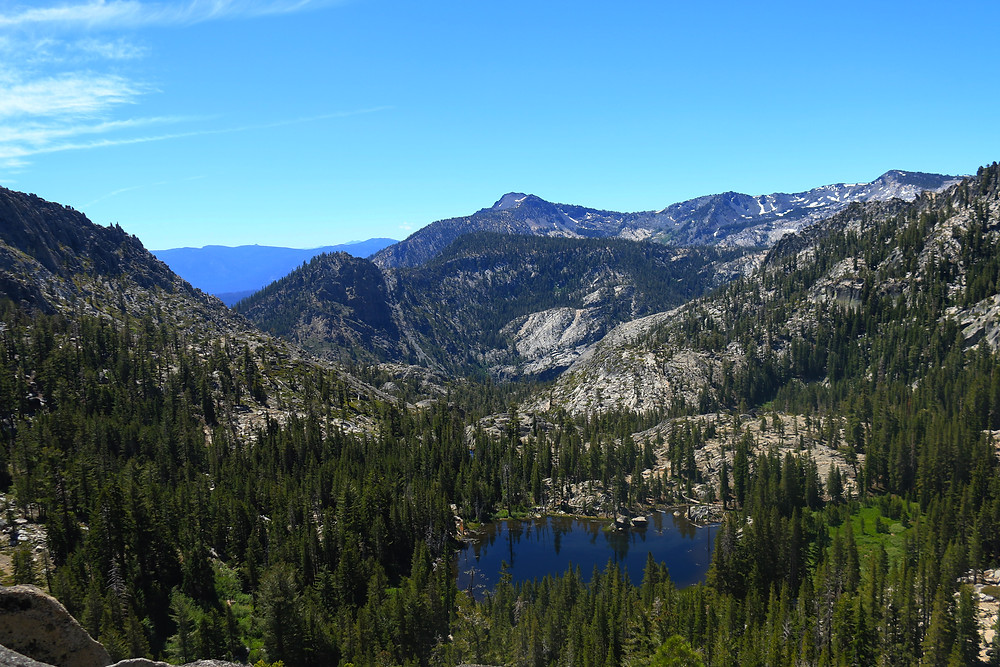 The view from Phipps Pass in the Desolation Wilderness near Lake Tahoe, California. Evergreen trees dot the hillsides, a dark blue lake sits in the middle. Blue skies are clear over grey mountainous terrain