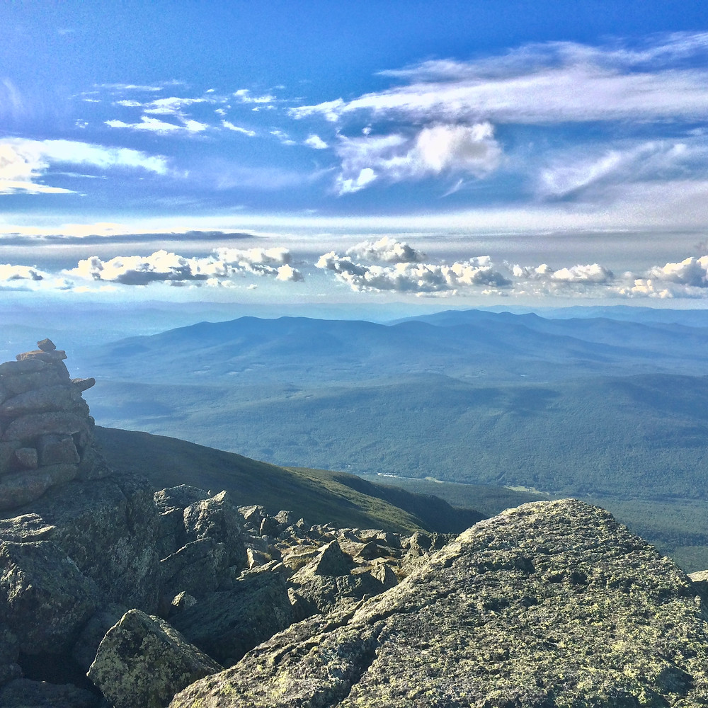 clouds fleck blue skies over the Presidential Mountains within White Mountains National Forest in upstate New Hampshire