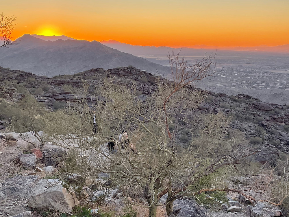The sun sets over the Superstition Mountains Northeast of Phoenix, Arizona, yet still firmly encased in the Sonoran Desert. The sun is blasting yellows and oranges across the entire horizon
