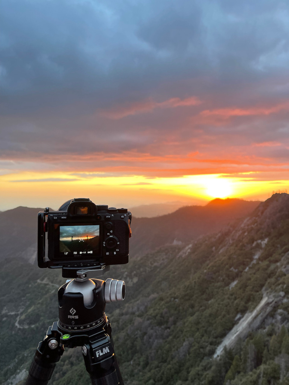 A striking sunset sends pinks and oranges bursting through the clouds. A camera is mounted on a tripod on top of a mountain side to capture this glory
