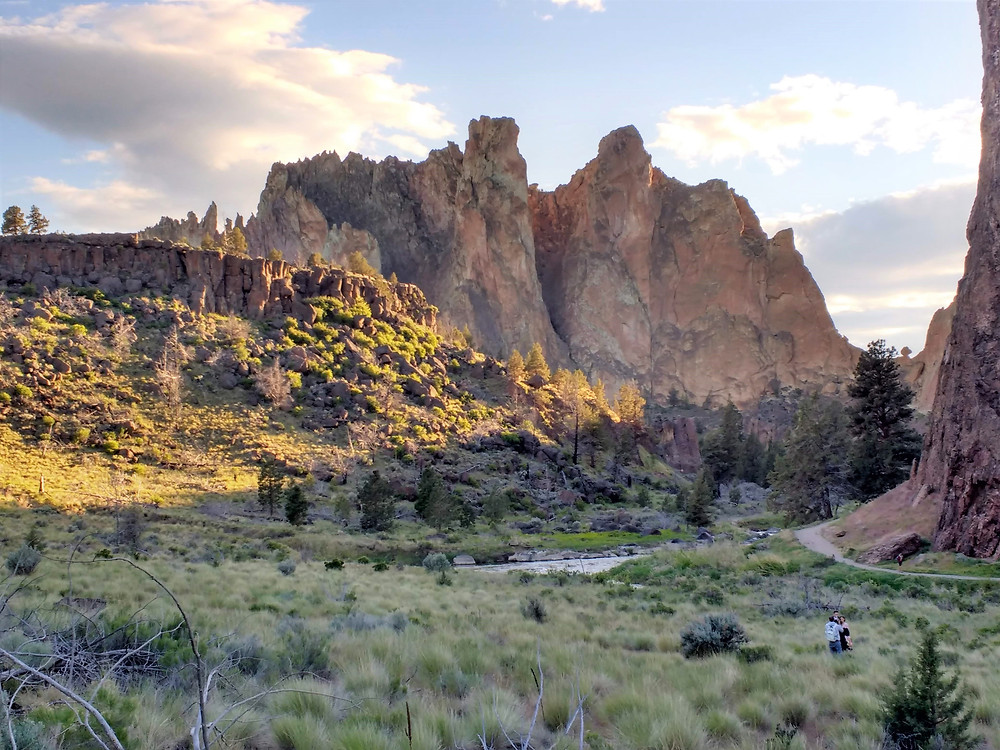 The sun beams down on a craggy bluff covered with yellow-green shrubs in the foreground, as the ruddy red cliffs of Smith Rock in Oregon loom in the background