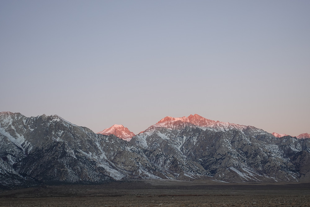 The sun kisses the tops of the mountains surrounding Death Valley National Park in southern California