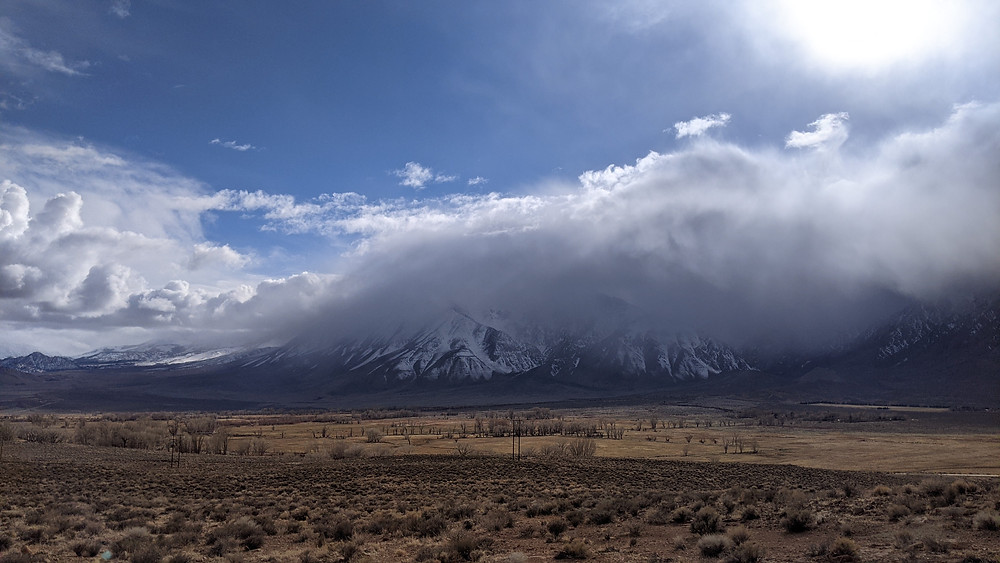 a low cloud dumps snow on a mountaintop in the background. In the foreground, a scrubland desert lies waiting for the onslaught of weather. The blue skies overhead won't remain so for long