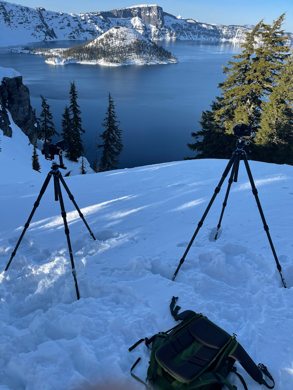 Snow covers Wizard Island and the shore of Crater Lake in Oregon. Two cameras are mounted on tripods on the shore to capture the majesty