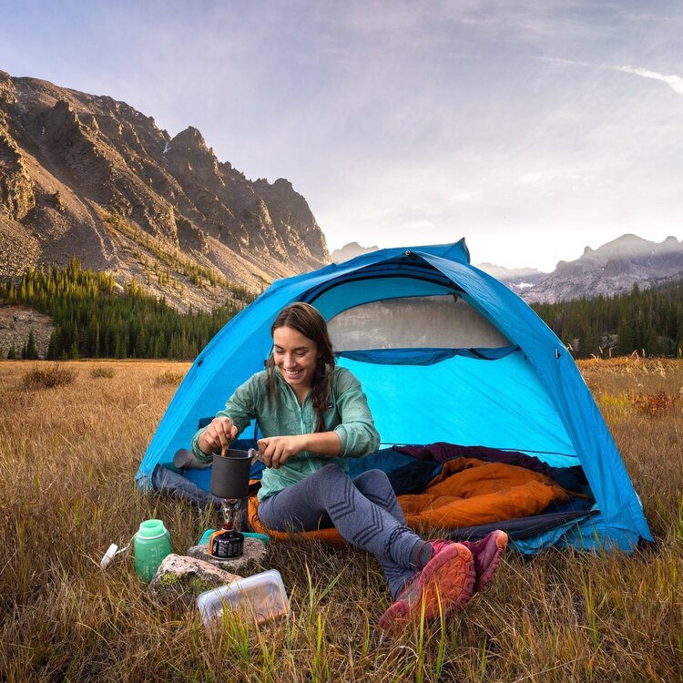 The chef behind Gritty  Gourmet, Karen Williams, cooks on a camp stove while sitting on the edge of her tent in a mountain valley