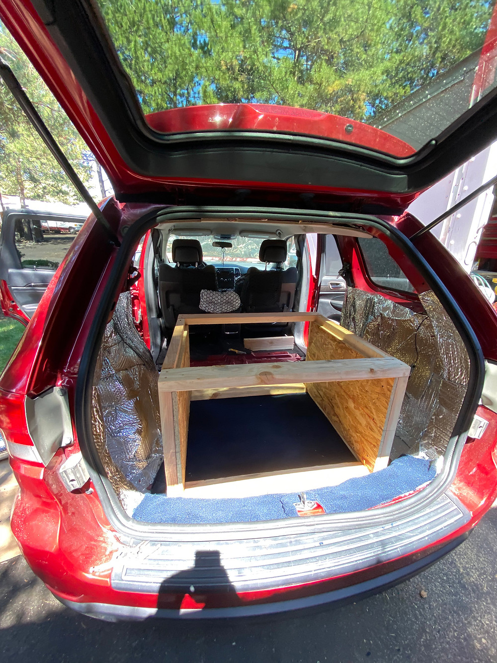 a red 2011 Jeep Grand Cherokee begins its transformation from soccer-mobile to a camper for Van Life. Here, the wooden foundation for the bed is laid down in the back, surrounded by silver insulation