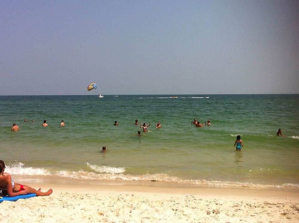 the sandy shores of the Gulf of Mexico in Southern Alabama. Beachgoers enjoy the warm water and watch the parasailer in the background