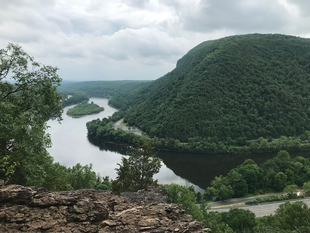 A lazy river winds through the Delaware Water Gap. The hills on each side are covered in trees