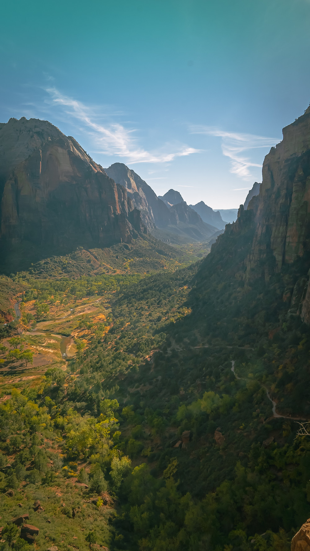 a birds eye view of Zion National Park in Utah. Craggy mountains under a blue sky, looming over a lush forest in the valley below