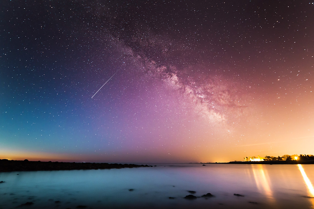 A meteor falls through a rainbow night sky over Rye, New Hampshire