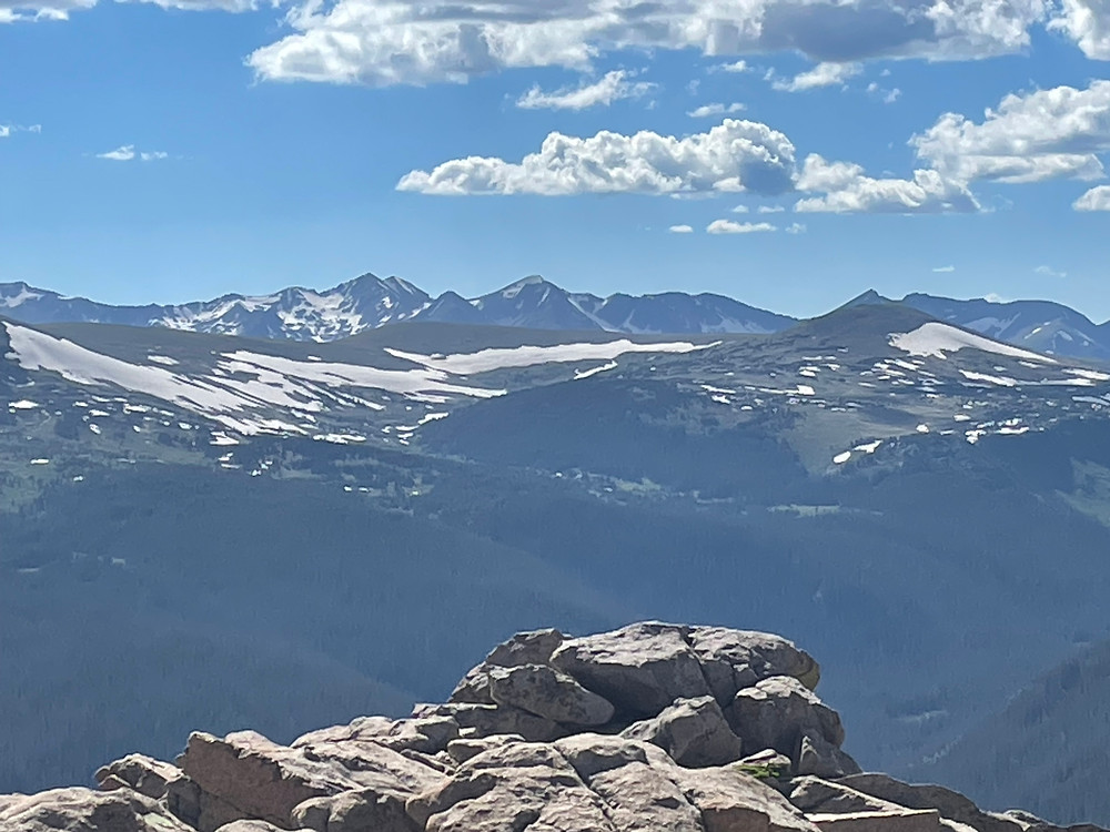 A jaw dropping view of snow capped mountains in the distance in Rocky Mountain National Park in Colorado. Way too much snow for a photo snapped in June.