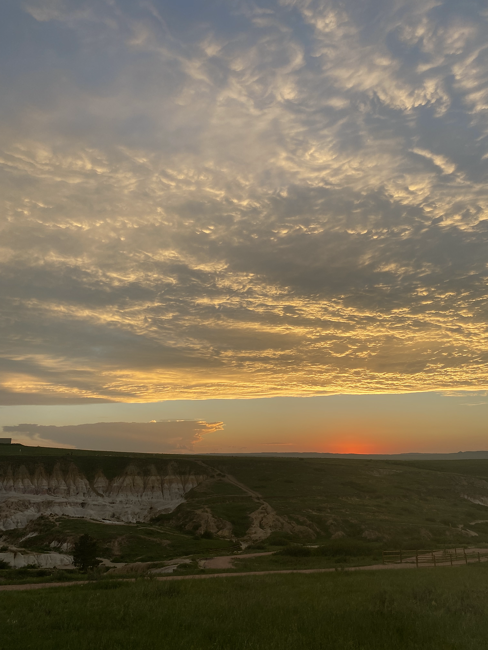A brilliant sunset stains the clouds overhead the alien rock formations of Paint Mines in Colorado