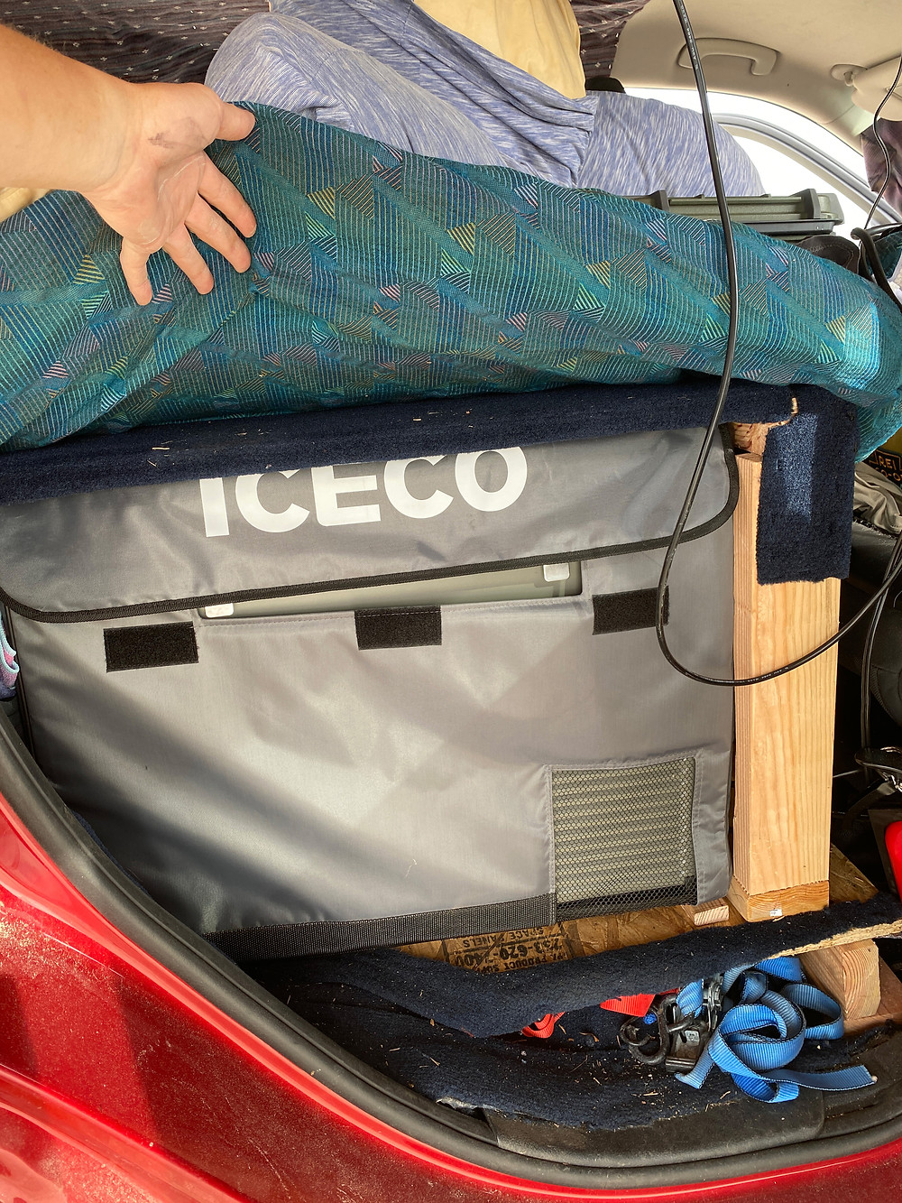 a red 2011 Jeep Grand Cherokee begins its transformation from soccer-mobile to a camper for Van Life. An Iceco portable refrigerator is installed in the back of the truck