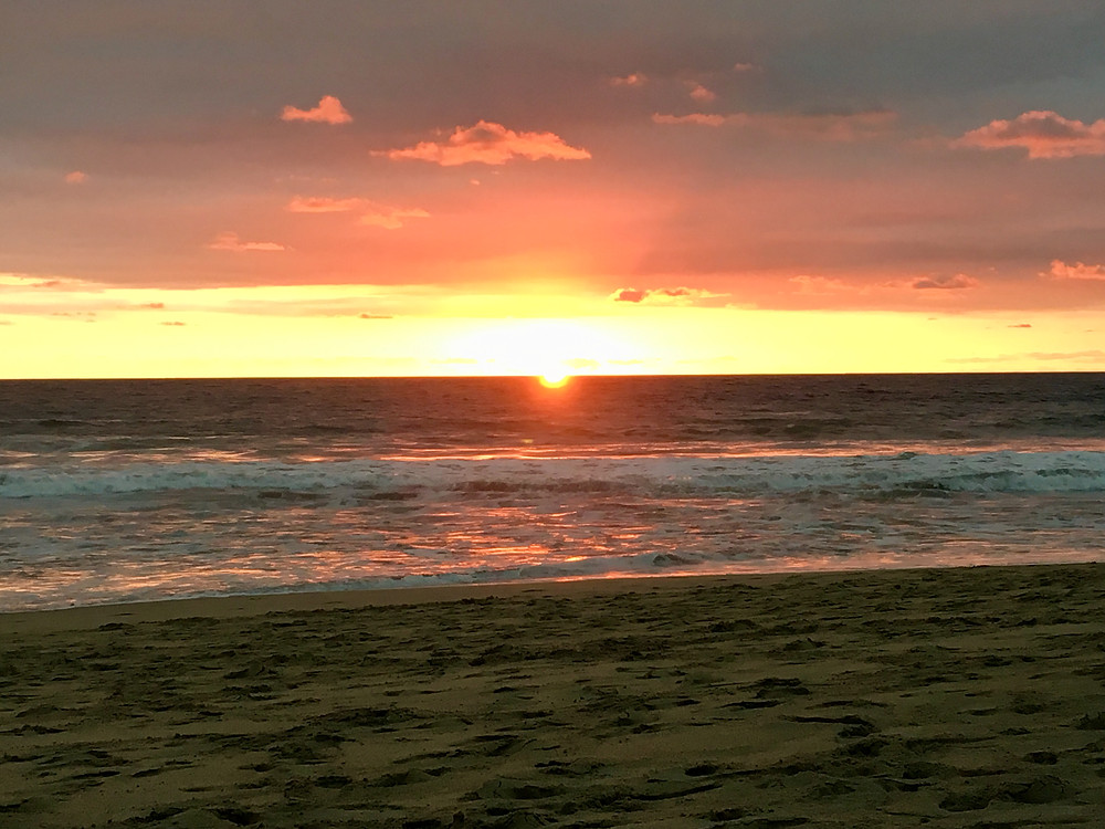 Sunset splashing pinks and oranges across the sky above Playa Zicatela in Puerto Escondido, Oaxaca, Mexico