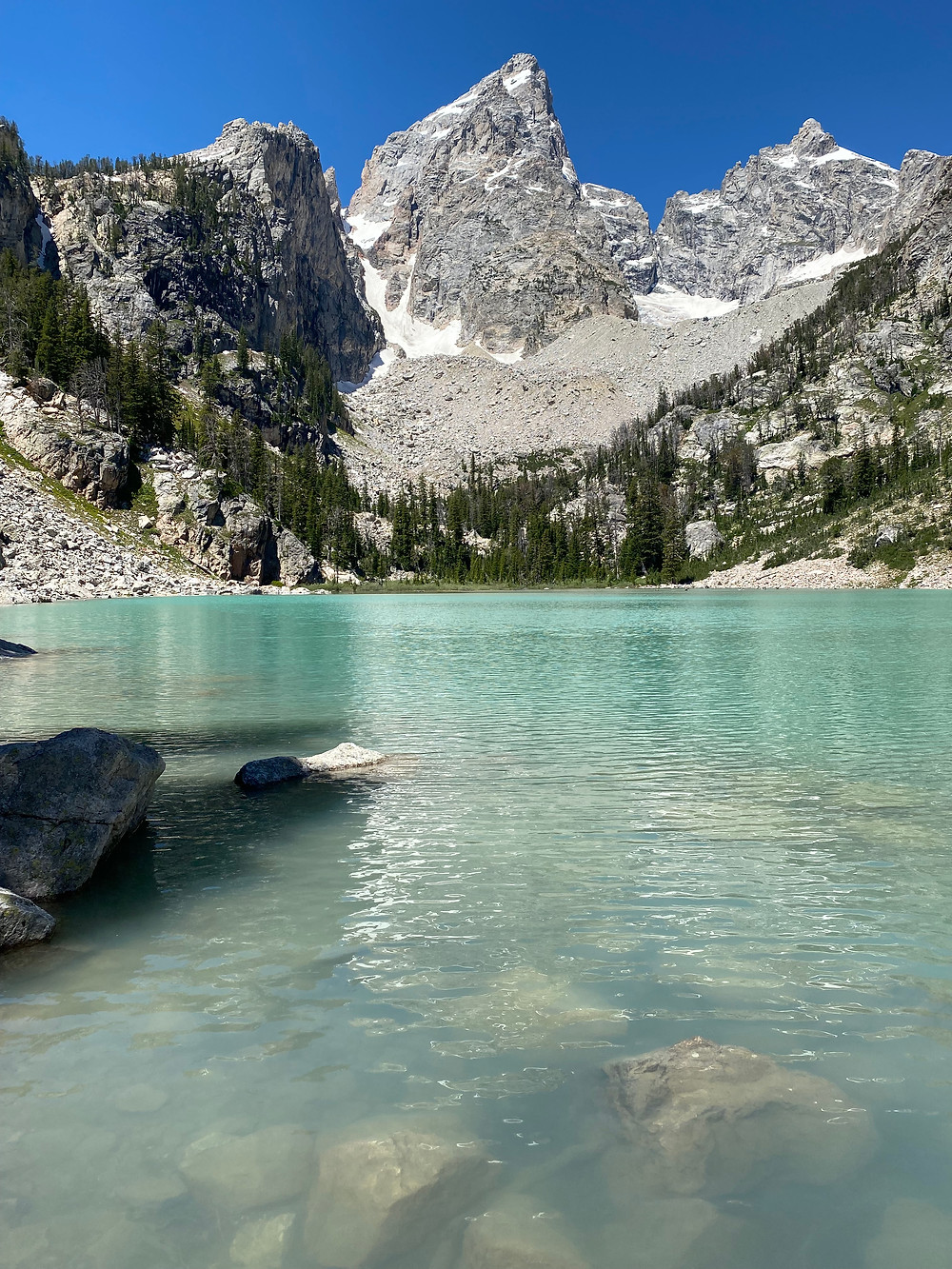 The blue-green waters of Delta Lake lay in stark contrast to the grey granite of the Grand Tetons and the blue skies overhead
