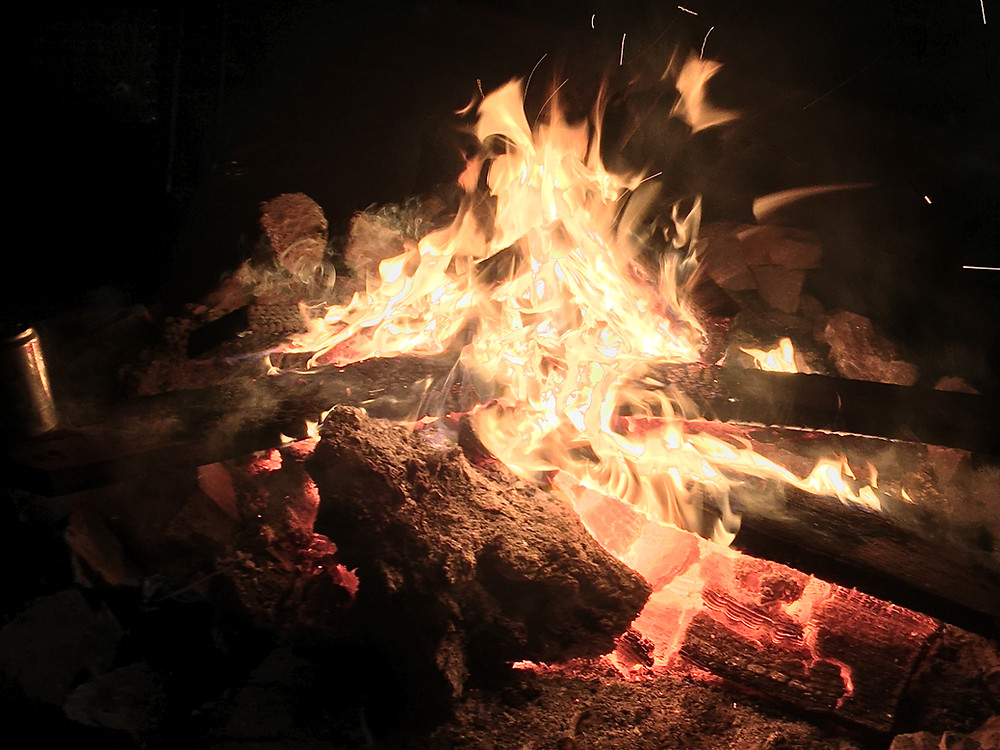 a close-up photo of a campfire - orange flames dance above deep red coals with brown logs feeding the flames - somewhere near Booneville in the Mendocino Mountains of California. There may or may not be a beer can off to the left