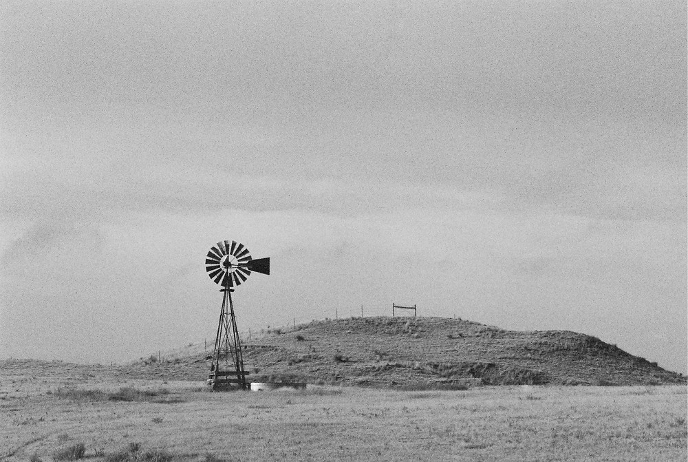 A black and white photo of a perfect representation of a Nebraska windmill on the Great Plains