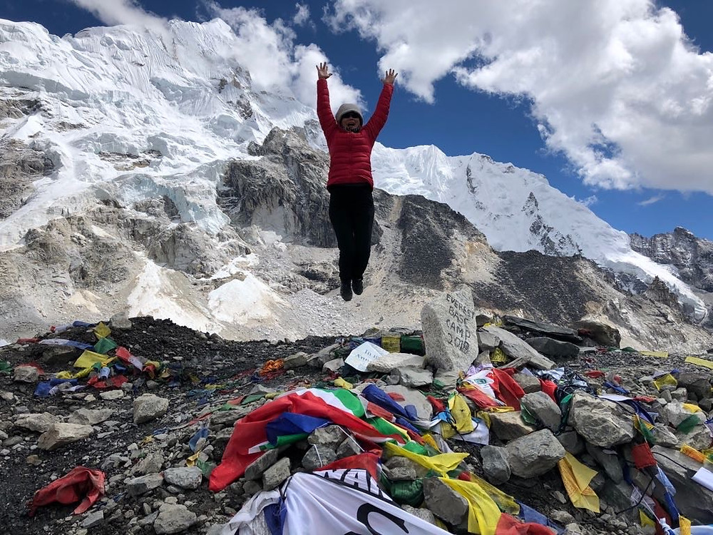a woman bundled up in an orange coat leaps for joy at the base camp of Mount Everest in Nepal, as the mountain looms tall, majestic, and covered in snow behind her