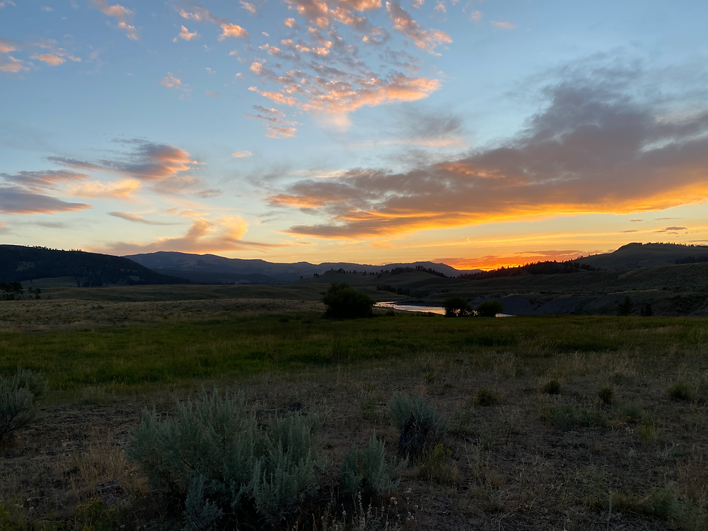 Sunset illuminates the clouds with oranges and yellows over the scrubby plains of Yellowstone National Park in Wyoming
