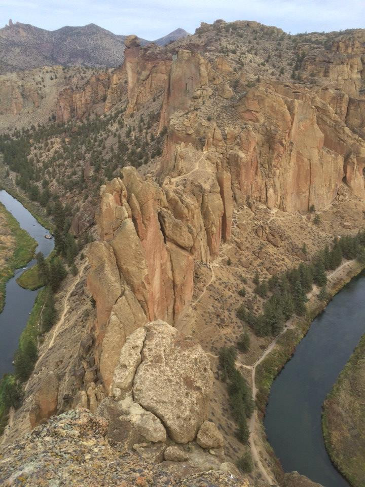 A view down on the reddish cliffs and crags of Smith Rock in all its majesty, abutted by rivers on both sides of the narrow cliff base