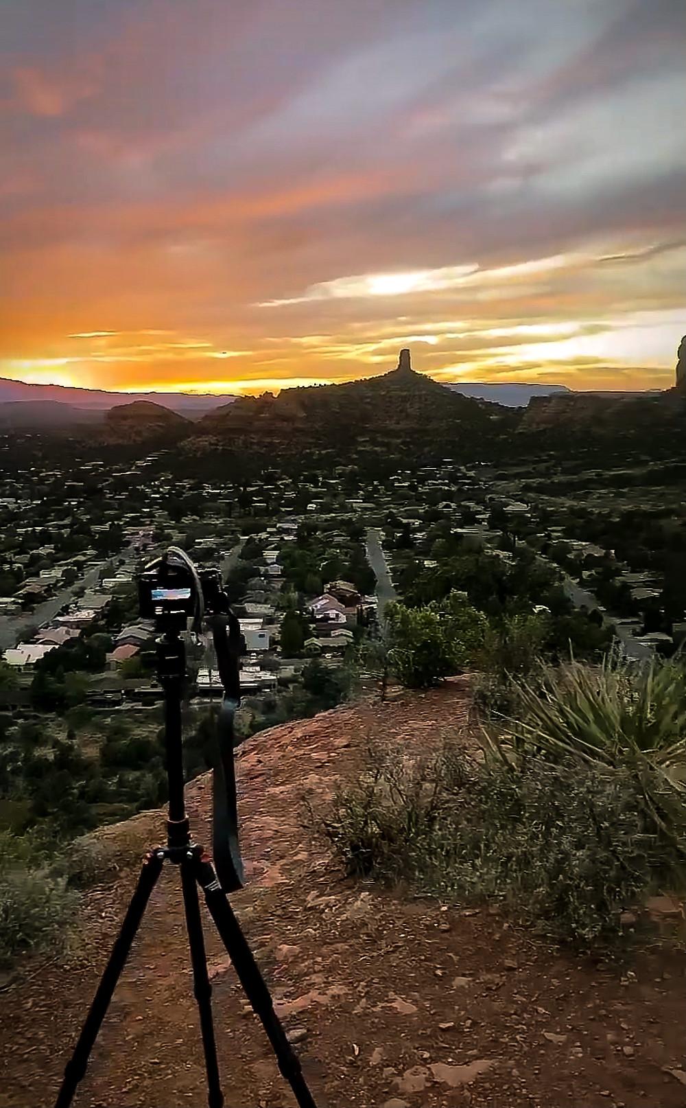 a camera on a tripod, set up to film a brilliant sunset over Devil's Bridge in Sedona Arizona