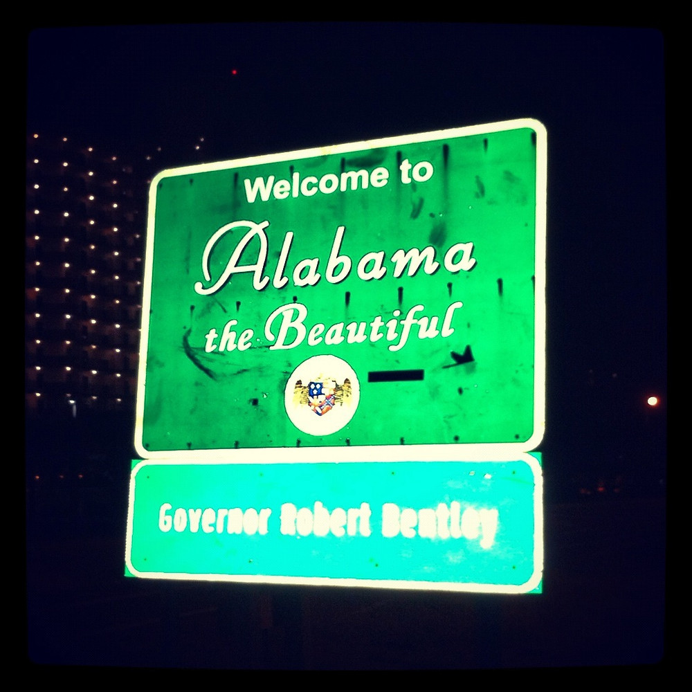 a green highlway sign welcoming you to Alabama, the beautiful