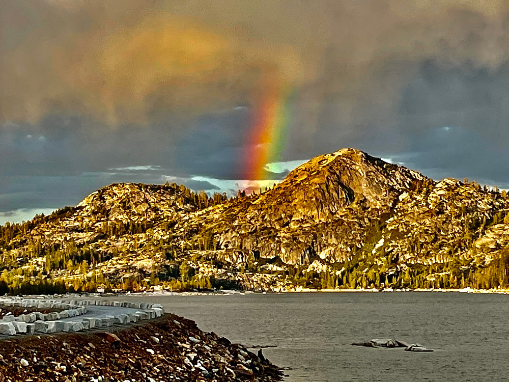 A rainbow beams down from cloudy skies over the Sierra Nevada Mountains in Eldorado National Forest, California. Loon Lake looks extremely cold in the foreground