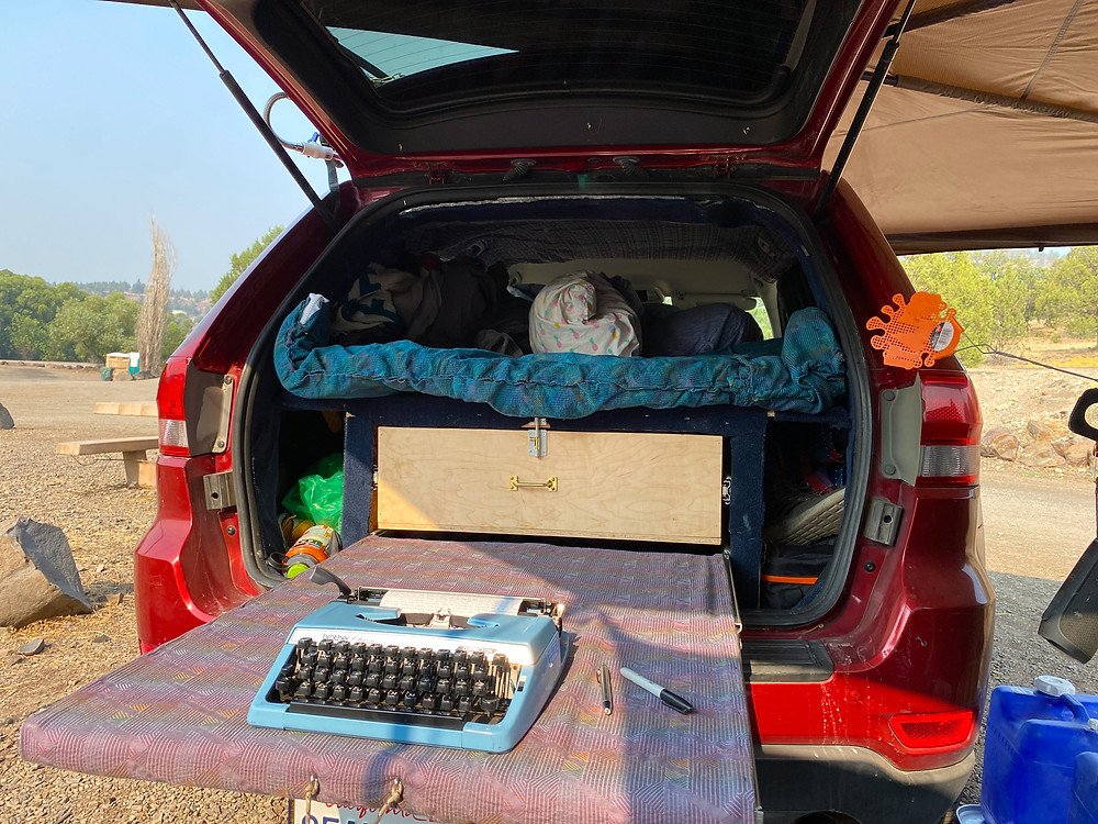 A sweet lil' blue typewriter is set up on a desk extending from the tailgate of a red Jeep Cherokee. Not a bad little office