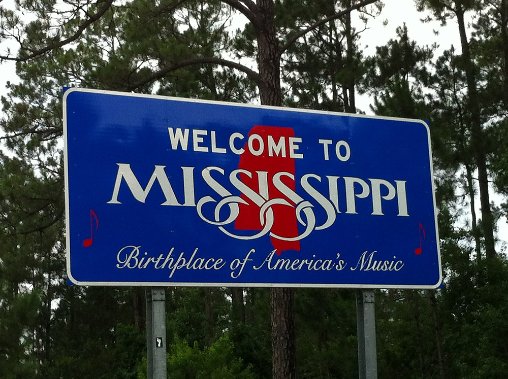 """A blue highway sign welcoming travelers to Mississippi, the """"Birthplace of America's Music"""" (move over, New Orleans, Chicago, New York, and everywhere else America's music was born)"""